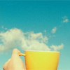 talkaloud: yellow coffe cup held in front of blue sky with puffy clouds by a disembodied hand (coffe cup sky)