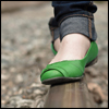 taennyn: low-angle view of a woman in folded-up jeans and green shoes walking along a railroad track. (Dorothy's got nothin' on these)