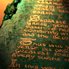 tangyabominy: A close-up of a shimmering green tablet from which gold lettering shines out. (emerald tablet)