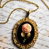 pyewackit: A gold necklace with a pendant that has a picture of a pink rose on it, placed over a piece of paper with writing on i. (Rose pendant)