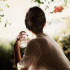 recessional: a dark-haried woman sits with her back to the camera and a glass of water in her hand (personal; backlight)