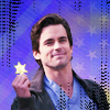 originalpuck: Neal Caffrey smiling and in scrubs, holding up the badge he found from a cereal box. (Neal With Cereal Badge)