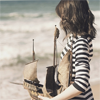 sunspot: girl in striped shirt holding a wooden boat (sailing ship)