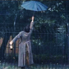 ar: Withnail from behind, thrusting an opened umbrella in the air while holding a bottle of booze. (w&i - man delights not me)