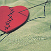 sympathetic_strings: A heart with stitches sewn up its middle by a needle and thick black thread. (mended)