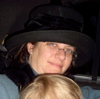 piglet: me, in fabulous winter hat & coat, smiling at camera over top of v. small son's head (thanksgiving)