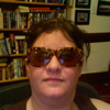 piglet: me in bangs, mona lisa smile, bug-eyed tortoise-shell sunglasses, in front of books & photos (march08)
