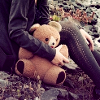 juushika: Photograph of the torso and legs of a female-bodied figure with a teddy bear. (Bear)