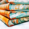 bookdesign_project: a stack of books with decorative, marbled patterns on the tailedge (book book)