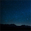 ravensflight: A picture of a starry sky set against a silhouette of low mountains (Default)