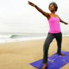 semielliptical: Black woman practicing yoga on a beach (yoga by the shore)