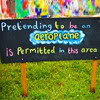 "debitha: A sign from a kids playground that says, ""Pretending to be an aeroplane is permitted in this area"" (Aeroplanes are OK)"