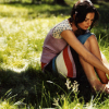 feuille: woman sitting on sunny grass by herself (girl alone in the grass)