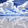 rhi: The sky reflected in shallow water and a person walking the two. (road less traveled)