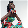 skywardprodigal: Beautiful seated woman, laughing, in Vlisco. (Default)