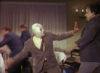 el_enmascarado_de_plata: Santo in a silver full face Spandex mask and brown suit and tie, punching a guy across the room (eject button for the human memory (color)
