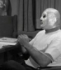 el_enmascarado_de_plata: Santo in a silver full face Spandex mask and white t-shirt, looking thoughtful (talking to Blue Demon (b&w))