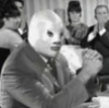 el_enmascarado_de_plata: Santo in a silver full face Spandex mask and suit jacket, clasping his hands and watching something offscreen (watching the terrible musical number (b&)