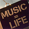 crossfade: A crop of a stinseled sign that says Music = life. (Holt)