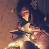 sylvaine: Girl wrapped in fairy lights with stars in her hair, reading a book. ([gen] read by fairy light)
