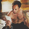 kabal42: Sherlock from Elementary, shirtless, sitting on the floor reading (Sex - JLM Sherlock shirtless on floor)