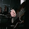 heuradys: closeup of Dom from Bell X1 playing bass, silver found H on wall behind (Default)