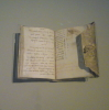 mirrorshard: Photo of a small leather-bound notebook, filled with mirror writing (WIP)