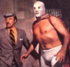 el_enmascarado_de_plata: Santo in a silver full face Spandex mask and some guy in everyday clothes, looking at something off camera to the left (something is coming from the left! (colo)
