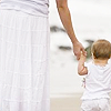 queenofhell: A woman in white, holding the hand of a small child also dressed in white. (Mother)