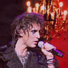 princesse_incongrue: Mikelangelo Loconte singing into a microphone in front of a red background (mikele rocking)