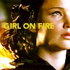 next_to_normal: Katniss in her flame costume; text: girl on fire (girl on fire)