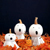 grey_gazania: three pumpkins painted white and given ghost faces in a bed of orange leaves (pumpkin faces in the night)