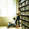daemonluna: Two people in front of a bookcase in the sun, reading (books reading stacks)