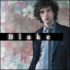 thesynchronomes: A man wearing a suit standing in front of a floral background, with text reading 'Blake'. (Blake)