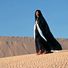 lireavue: A woman in a long black cloak walking through the desert (lady of dreams and shadows)