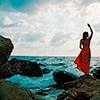 lireavue: A woman in a red dress, one arm raised in greeting, standing on the rocks facing out to the ocean. (where the sky and water meet)