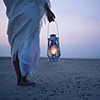 lireavue: A person dressed in white on the beach pre-dawn, carrying a lamp. (diogenes with his lamp)