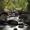 amandaw: A river strap runs toward the camera, over large round rocks, starkly back-lit by setting sunlight. (Default)