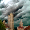 derridian: image of a city with storm clouds behind it (storm city)