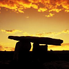 mokie: A dolmen silhouetted against a golden sunset (spiritual, calm, bittersweet, nature, witchy)