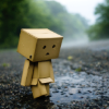 mokie: A tiny, sad cardboard robot walks in the rain (sad, depressed, disconnected, pessimistic, thwarted)