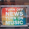 "delight: TV screen reading ""turn off news, turn on music"" (music > news)"