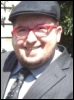 tim: Tim wearing a flat cap and a gray/black suit (Default)