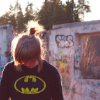 alexiel_neesan: girl in a batman sweatshirt with background of tagged bunker and trees (Default)