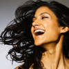 signifier: a dark-skinned woman laughs with her hair flying (Qadeen: Alanne/Zira (Beloved Assassin))