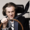 littlemoose: A photograph of James May sitting in a car seat in a white studio, holding a steering wheel. (TG - May: Windswept)