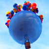 littlemoose: A blue hot air balloon covered in smaller, brightly coloured helium balloons, against a blue summer sky. (TT - Circus: lonely balloon)