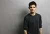 josephine_marrs: Colin Morgan, dressed in a dark gray shirt against a light gray background (pic#6408568)