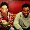 petra: Two guys sitting on a couch, one eating, one grinning (Troy & Abed - Watching tv)
