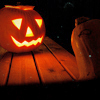 vorpal: Photo of a jack-o'-lantern glowing on a porch in the dark (Halloween)